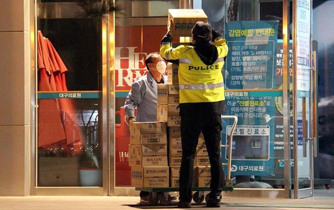 대구의료원을 순찰 중인 경찰이 의료진의 물건을 옮겨주고 있다.